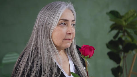 Attractive portrait of dreamy modern 60-aged woman with long gray hair which Live Action