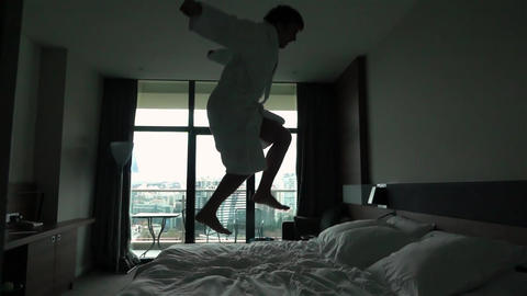 Happy Young Man jumping on bed at hotel in bathrobe Live Action