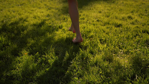 Young attractive woman feet running by grass in park, barefoot Live Action