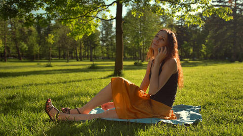 Woman sit on green grass and have conversation via selfphone Live Action