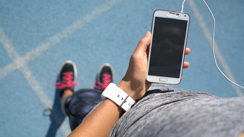 Runner girl using smartphone touching screen choosing music for running on track Live Action