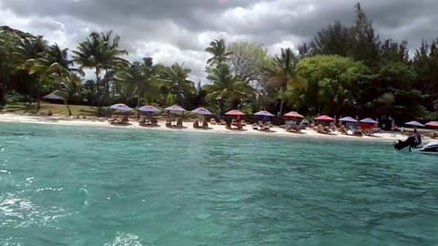 View of a beach and crystal clear waters on a sunny day, Mauritius, Indian ocean Live Action