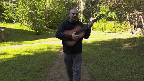Man playing guitar and walking on the path Footage