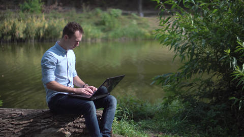 Young attractive man working on computer in the park Footage