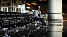 Woman sit alone at empty row of seats, answer on phone, terminal lounge Footage