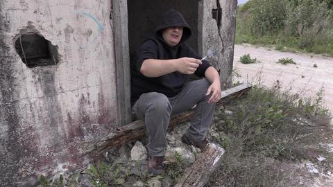Drug addict man offers syringe near abandoned building Footage