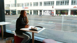 Young woman enjoy hot drink, sit in cafe near big glass window, Helsinki Footage