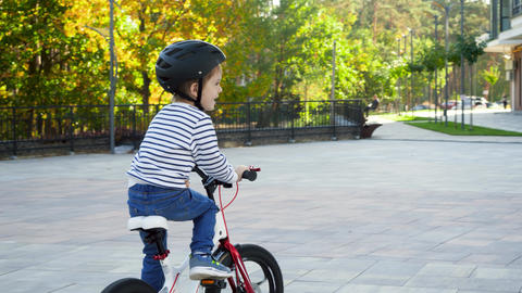 4k video of happy cheerful little boy learning and riding bicycle on city street Live Action