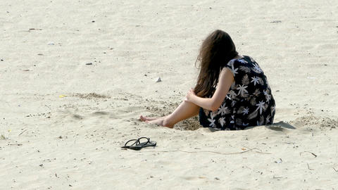 Anon girl sitting playing with sand Live Action