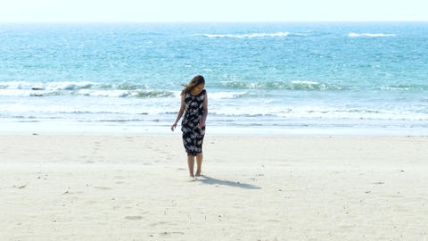 Girl walking to camera from beach Live Action