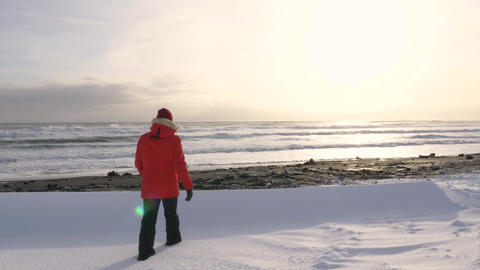 A young man walks along the coast of the Pacific ocean in winter 007 Live Action