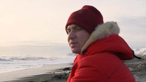 A young man walks along the coast of the Pacific ocean in winter 012 Live Action