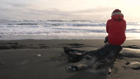 A young man walks along the coast of the Pacific ocean in winter 009 Live Action