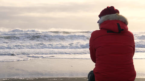 A young man walks along the coast of the Pacific ocean in winter 011 Live Action