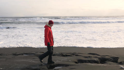 A young man walks along the coast of the Pacific ocean in winter 014 Live Action
