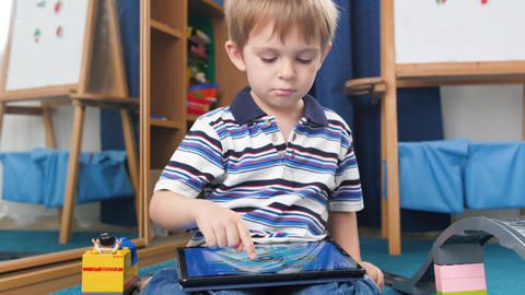 4k video of funny little boy playing educational video games on digital tablet Live Action
