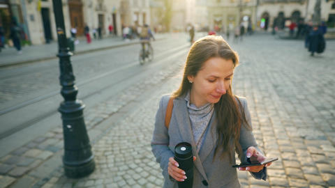 Woman with a thermos cup in hand walking down an old street using smartphone at Acción en vivo