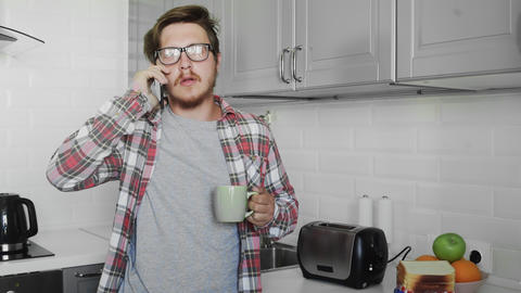 Young man with cup of tea talking on the phone at home GIF