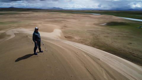 Drone fly around a tourist standing on top of sandy barkhan Live Action