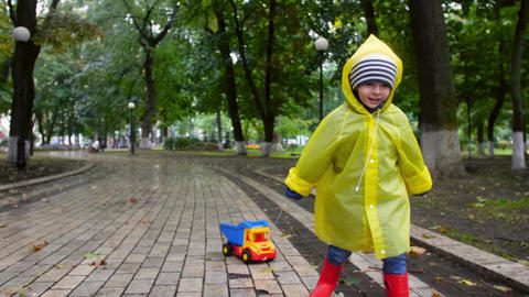 4k video of cheerful laughing little boy in raincoat running in wet autumn park Live Action
