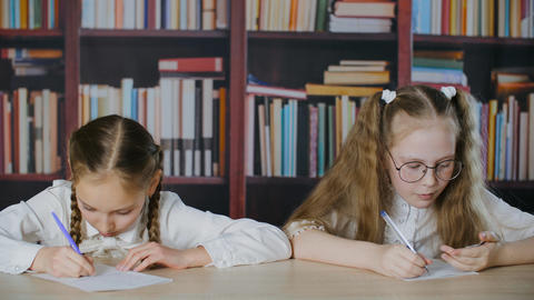 Worried small girl cribbing from paper during exam GIF