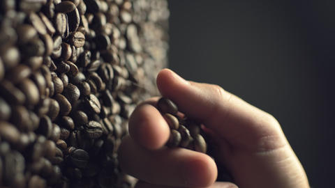 Closeup of coffee beans scatter out of male's hand in slow motion Live Action