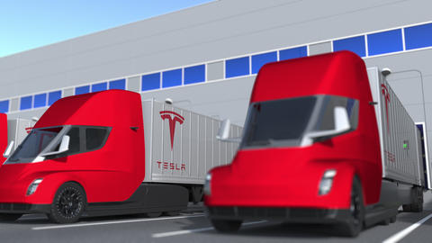 Modern electric semi-trailer trucks with Tesla logo being loaded or unloaded at GIF