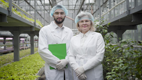 Portrait of young Caucasian man and senior woman in workwear standing in Live Action