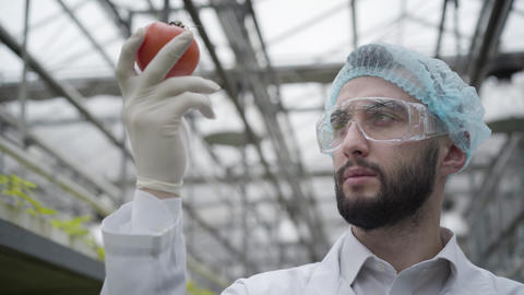 Close-up portrait of serious Caucasian man in protective eyeglasses examining Live Action