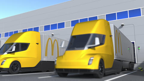 Modern trailer trucks with McDonald's logo being loaded or unloaded at warehouse GIF