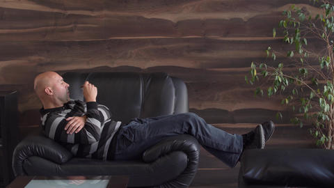 man relaxes with a mug of coffee in his hand on a black sofa in a luxury Live Action