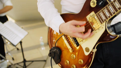 musician in white shirt plays guitar in shopping mall close GIF