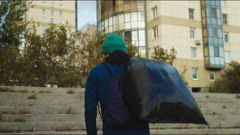 volunteer carries large garbage bag on city street steps Live Action