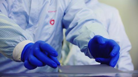 employees cover solar panel cell with material in workshop Acción en vivo