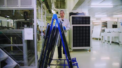 worker transports rack with solar panels along workshop Live Action