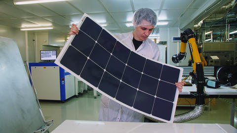 skilled worker bends solar panel near white table at plant Live Action