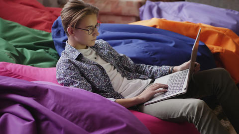 A teenage boy with glasses using a laptop Live Action