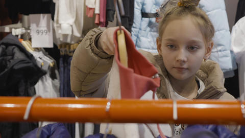 Young teenager girl looking jacket in clothes showroom at shopping. Young woman Live Action