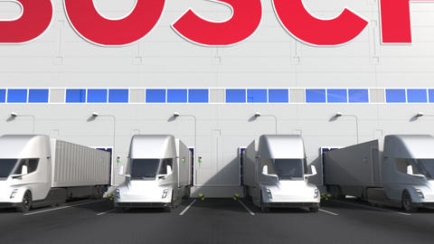 Electric semi-trailer trucks at warehouse loading bay with BOSCH logo on the Live Action