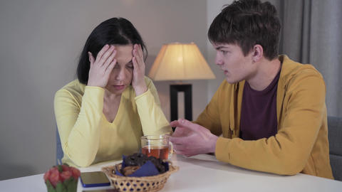 Stressed Caucasian mother holding head in hands and looking at teenage son Live Action