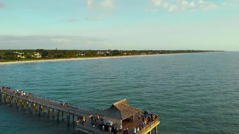Tourists watch sunset from the pier, aerial view Live Action