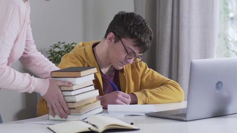 Portrait of smart Caucasian boy in eyeglasses looking at stack of books brought Live Action