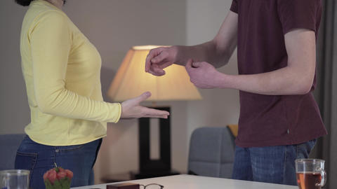 Two unrecognizable Caucasian people arguing indoors. Mother and son gesturing Live Action