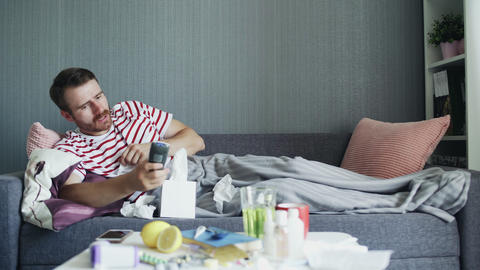 Sick man with flu at home, ill young man with fever watching tv show and using GIF
