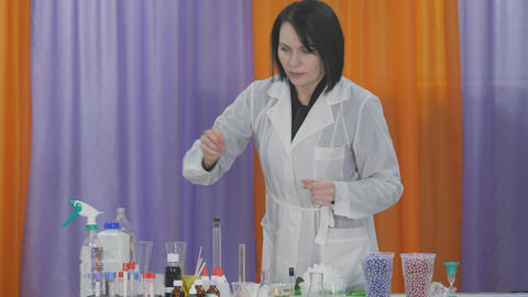 Chemist prepares ingredients for chemical experiments. Woman conducts cognitive Live Action