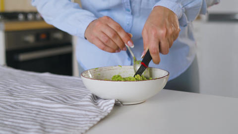 Woman chopping avocado in bowl to make healthy vegan breakfast Live Action