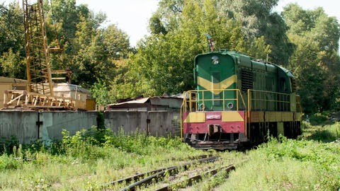 4k video of riding old diesel locomotive train near big metal scrapyard. Concept Live Action