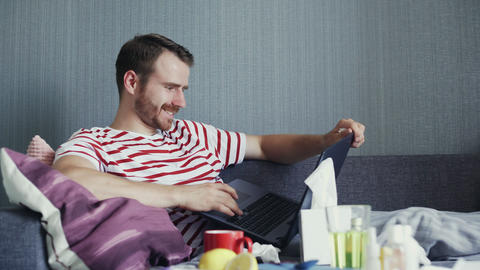 Sick bearded man using laptop and blowing nose with handkerchief GIF