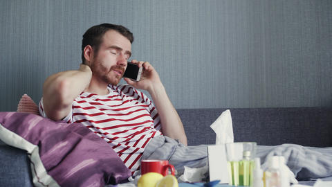 Sick young man talking on the phone at home GIF