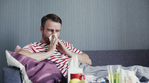 A man coughs heavily, blowing his nose while sitting on a couch in the living GIF